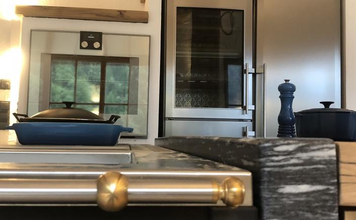 Luxusküche mit Backofen von Gaggenau, Side-by-Side Kühlschrak von Liebherr und Kloss Wohnherd sowie gemauerte Küche im Luxuschalet mit Eichenplatte